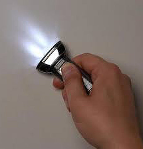 A person's hand is shown holding the lit-up flat flashlight.