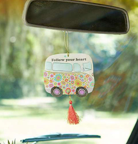 "The ""Follow Your Heart"" Car Air Freshener hangs inside on a rearview mirror in the car."