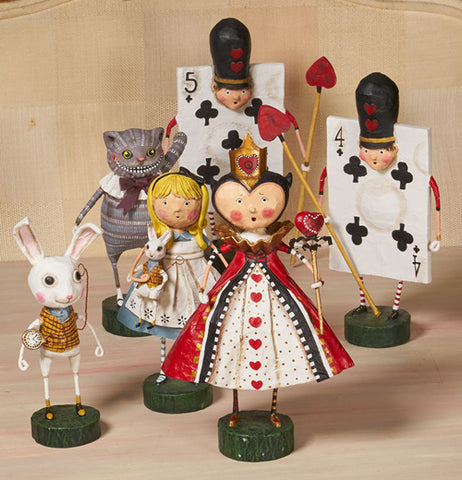 The Four of Clubs figurine sits with other figurines from Alice In Wonderland on a wooden table.