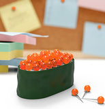 A container shaped as a sushi roll having orange tacks to resemble fish eggs set in an office setting.