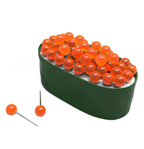 A container shaped like sushi with orange tacks that are made to resemble fish eggs sticking from the top with couple laying next to it.