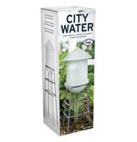 Box displaying the white watering tower dispenser in a garden.