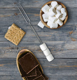 skewer laying on a wood patio alongside a bowl of marshmallows and graham crackers and someone's shoe poking in at the bottom.