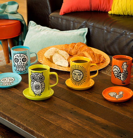 The green mug with the white owl design is shown lying on a wooden table next to three other mugs with similar designs.