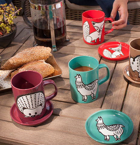 The Teal llama mug and coaster are shown next to two cups and coasters, one dark red with a hedgehog design, the other teal with a llama design.