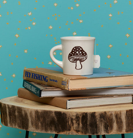 White mug with a brown mushroom on a stack of books sitting on top of a table made form a slab of wood with a teal wall behind that is spotted with yellow dots