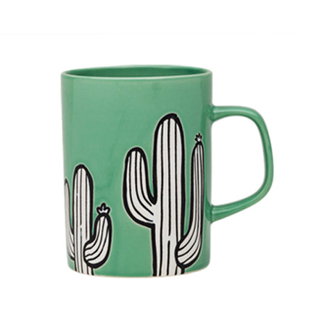 Green porcelain mug with white and black cactus design on a white background.