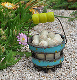 The Mini Egg Basket lays outside at the garden next to some green grass and some pink and yellow flowers.