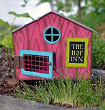 The mini rabbit cage is shown sitting against a small fairy garden background with grass in front of the cage.