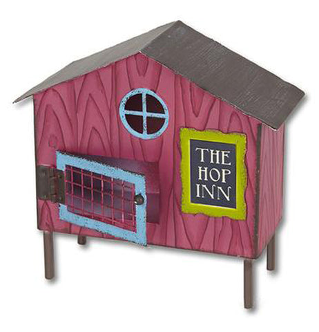 "This small sculpture is of a magenta rabbit cage with a blue door and window. To the right of the door is a black sign with a green outline. The words, ""The Hop Inn"" are in white lettering."