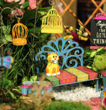 Both mini Garden Bird Cage picks are shown hanging in a mini garden along with a colorful bench that has a yellow cat sitting on it.