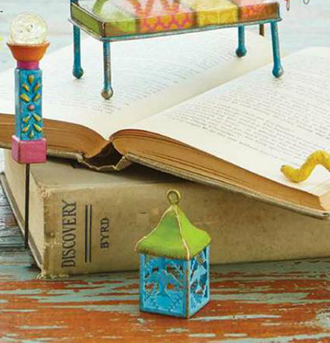 "The ""Mini Bird Lantern"" sits on the table with the ""Mini Lamp Post"" standing against the closed book and the ""Mini Bench"" sitting on the opened book."