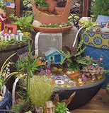 A large fairy garden display showing several different themes in many planters, the main one has a blue treehouse with flower stepstones and a red hammick.