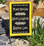 "The ""Plant Smiles"" mini sign stands in the fairy garden with the rocks."