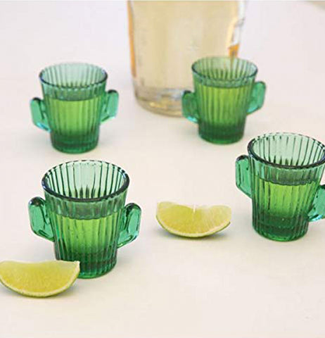 Four cactus-shaped shot glasses are shown sitting on a table next to a large glass pitcher, and two lime wedges.