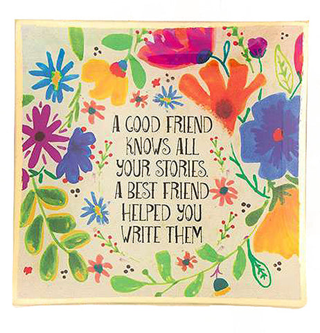 "A cream colored glass tray with multi-colored flowers all around a saying that says ""A Good Friend Knows All Your Stories A Best Friend Helped You Write Them."""
