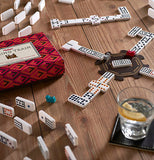 The game box is shown surrounded by dominoes set on their sides with several dominos in play on the train hub with a glass of water next to them.
