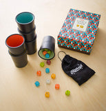 The Liars' dice game with the different colored cups, dice, and the black and white bag is shown lying on a wooden table.