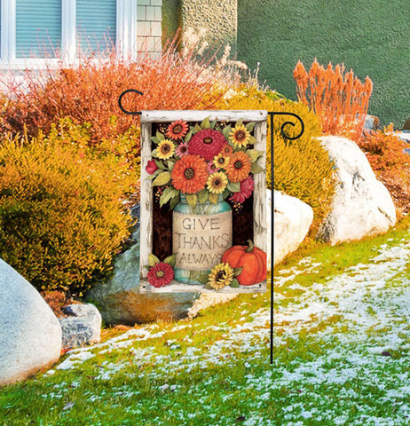 "The ""Give Thanks Always"" garden flag is shown pegged outside the front of someone's house surrounded by a small amount of snow."