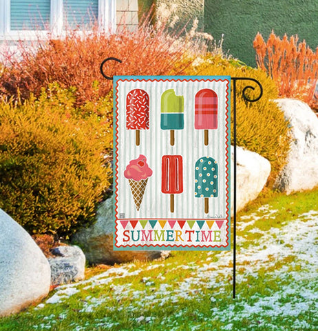 "The ""Summer Time"" Garden Flag hangs outside in front of a house and bushes."