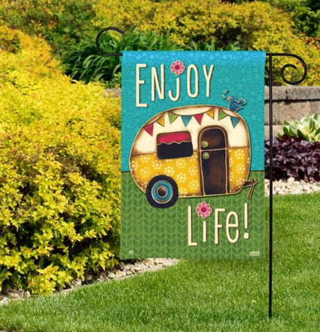 "The ""Enjoy Life"" Camping garden flag is shown pinned on the lawn outside the house."