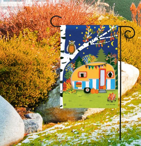 "The ""Fall Camping"" garden flag is pinned on the lawn outside the house with a little snow surrounding it."