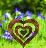 Copper triple heart spinner with chain and hook hanging up in a garden with purple flowers and green grass.