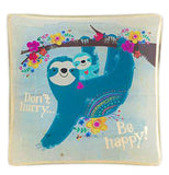 Square glass tray with image of a blue sloth and cub hanging from a flower lined tree branch with the words Don't Hurry Be Happy in gold foil.