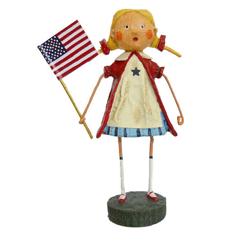 Gloria the figurine wears a red, white, and blue dress while holding a red, white, and blue American flag.