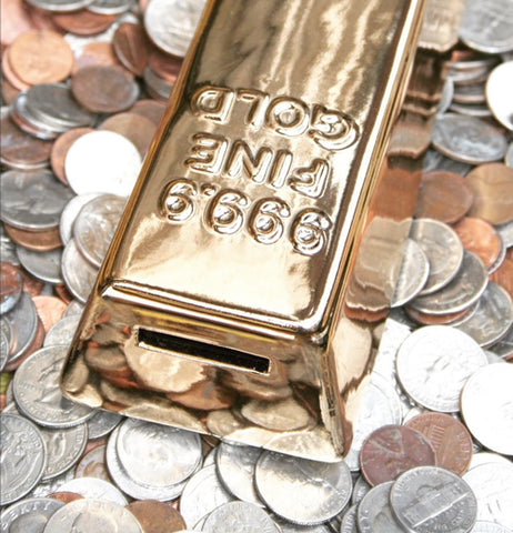 "The ""Gold Bar' Coin Bank lays on a pile of coins."