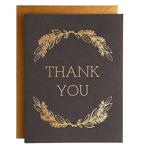 "This gold leaf foil card says ""Thank You"" printed on it in gold foil with a brown background it has a gold foil envelope."