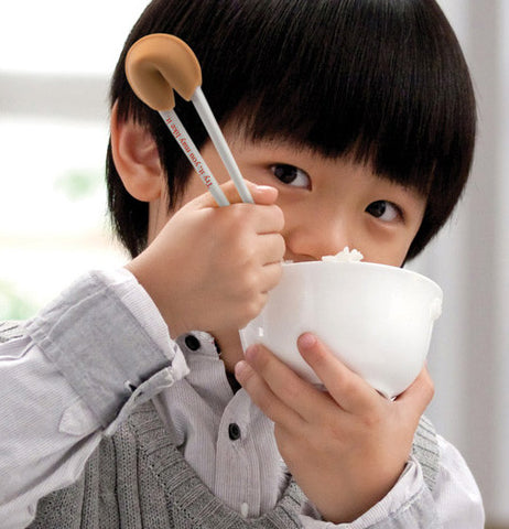 Boy eating rice with these fortune cookie chopsticks.