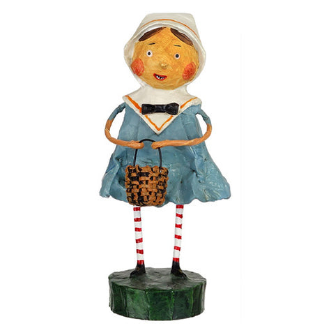 This Goodie figurine wearing a blue dress and white hood is shown holding a brown wickerwork basket.