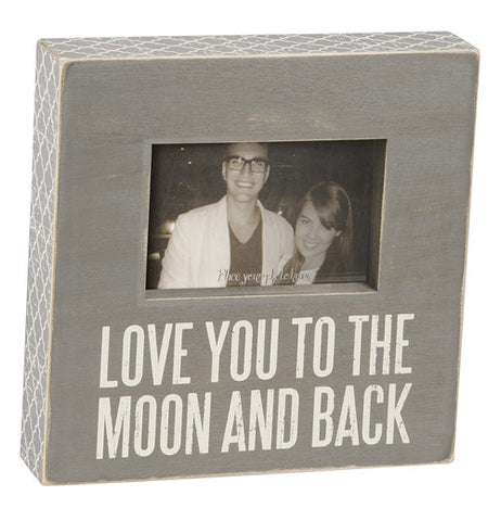 "A grey photo box sign says ""Love you to the moon and back""."