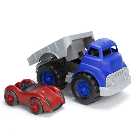blue and grey flatbed truck with the bed tilted back with a red racing car next to it