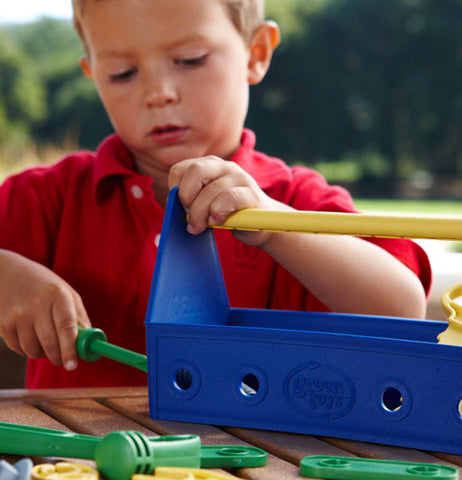 A child playing with a plastic tool set.