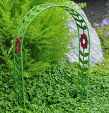 This green metal arch way with magenta flower with green foliage in the background