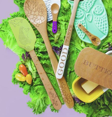 The green spatula with the hedgehog picture on its head is shown mixed with other spoons and spoon holders all sitting on grass.
