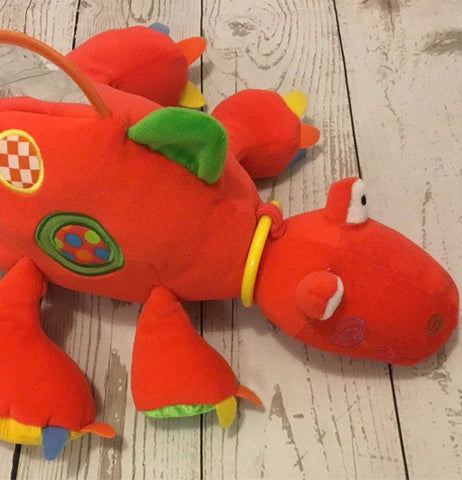 red dino with colorful spike stuffed animal on wood