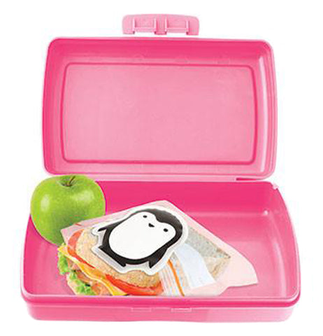 The penguin-shaped ice pack is shown inside a pink lunchbox with a sandwich and a green apple.