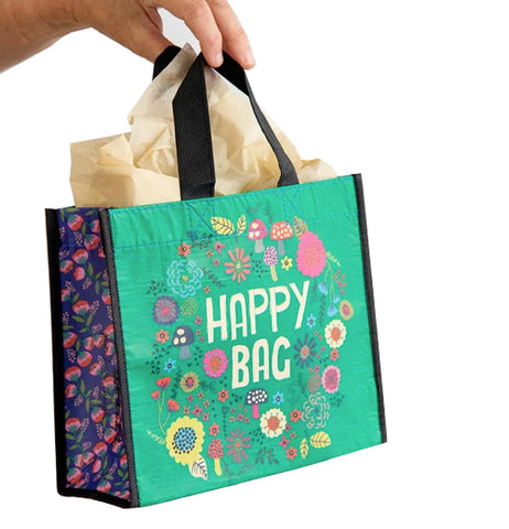 "Hand holding a green ""Happy Bag"" with mushroom and floral design by its black handles."