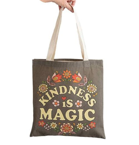 "a hand Carrying a floral patterned ""Kindness Is ""Magic"" Tote Bag."