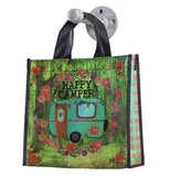 "Gift Bag that says ""Happy Camper"" with blue and pink and red flowers surrounding it with trees in the background."