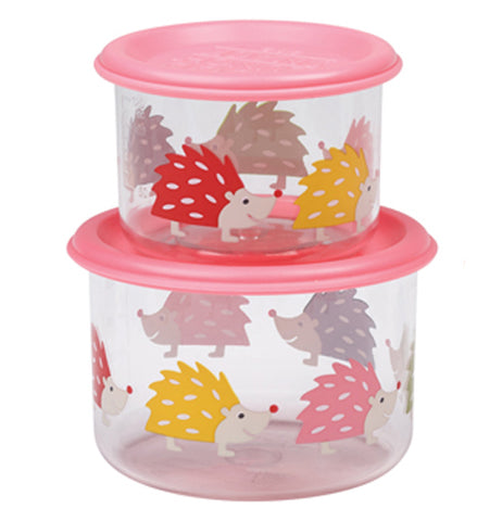 These two glass containers both have pink lids and different colored hedgehogs on them. One of them is small, while the other is somewhat bigger. The small one sits on top of the larger one.