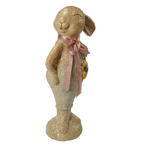 A statue of a smiling beige bunny with a pink ribbon.