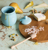 Wooden serving tray with cheese, honey pot, lid and honey dipper.