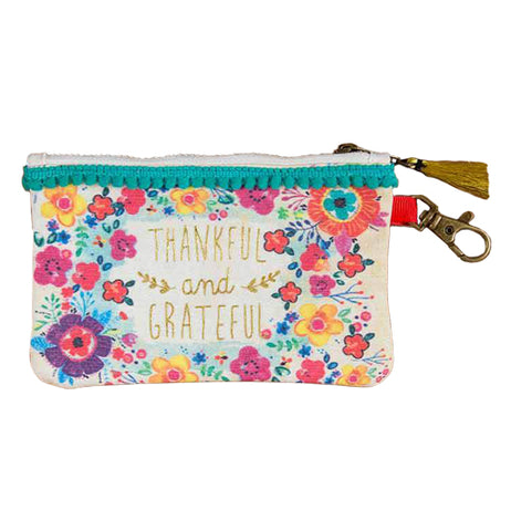 "This white pouch with a golden tassel hanging from its zipper has the the words, ""Thankful and Grateful"" in gold lettering. Surrounding the words are a series of magenta, purple, and yellow flowers."