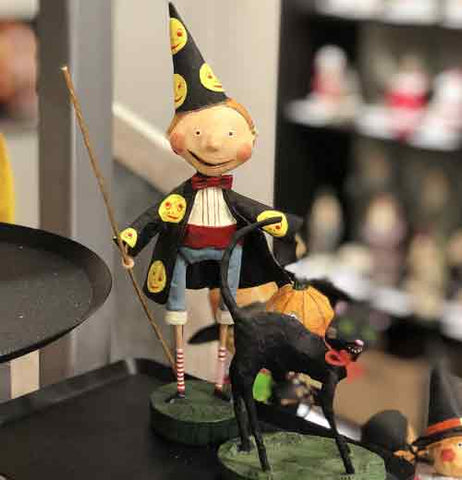 The sorcerer figurine is shown sitting on a shelf next to a black cat figurine.