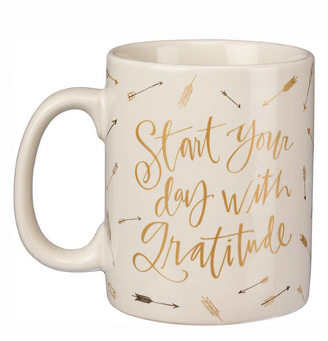 "A cream colored coffee with the phrase ""Start your day with gratitude"" in golden lettering"