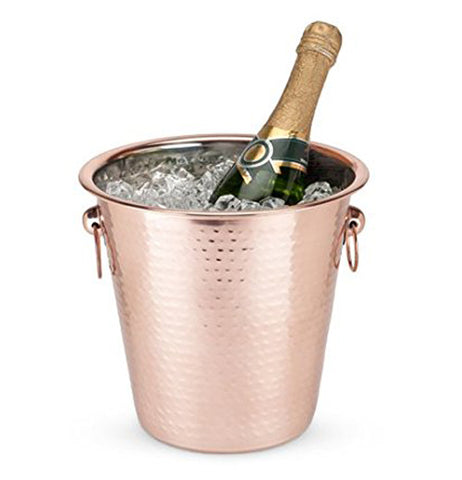 Hammered copper ice bucket with ice and bottle of champagne with handles.